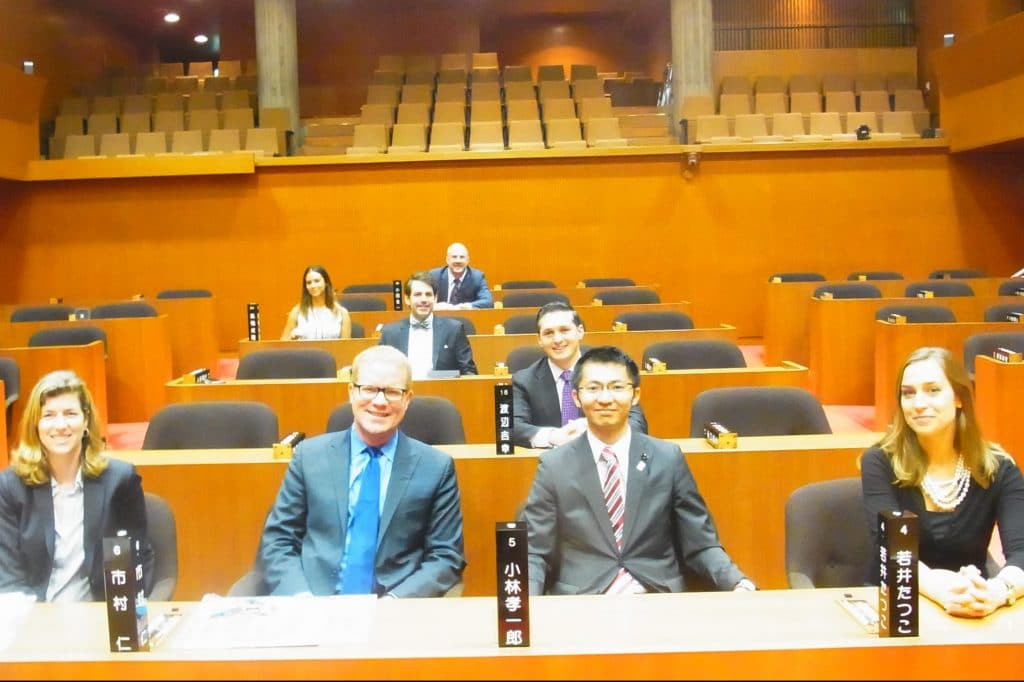 Delegation members try out the seats in the Okayama Prefectural Assembly chambers with Assembly Member Koichiro Kobayashi.